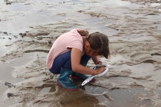 Girl muddipping on Fylde Coast